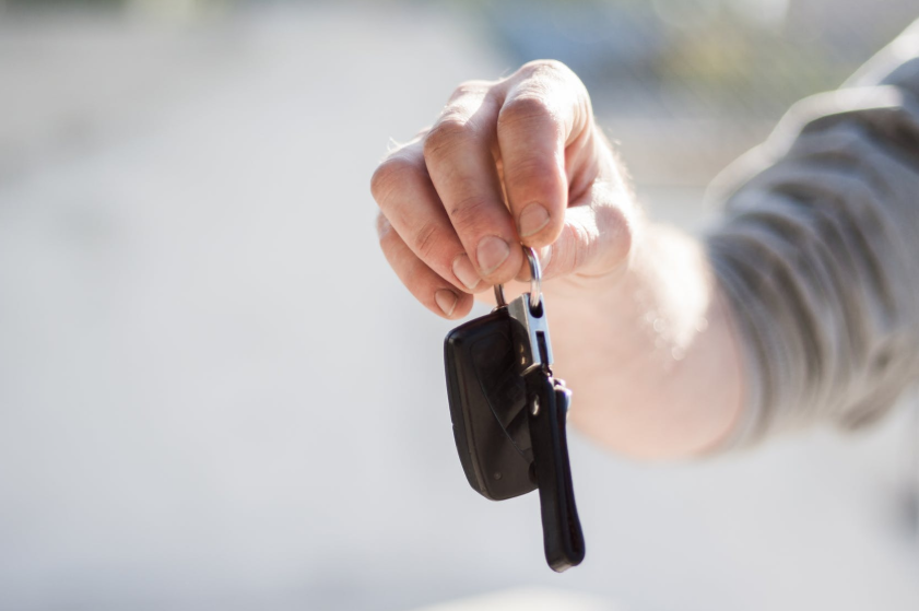 A man hands over some keys to a new car buyer