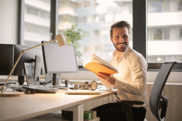 A man smiles at his desk and looks full of energy in the work place