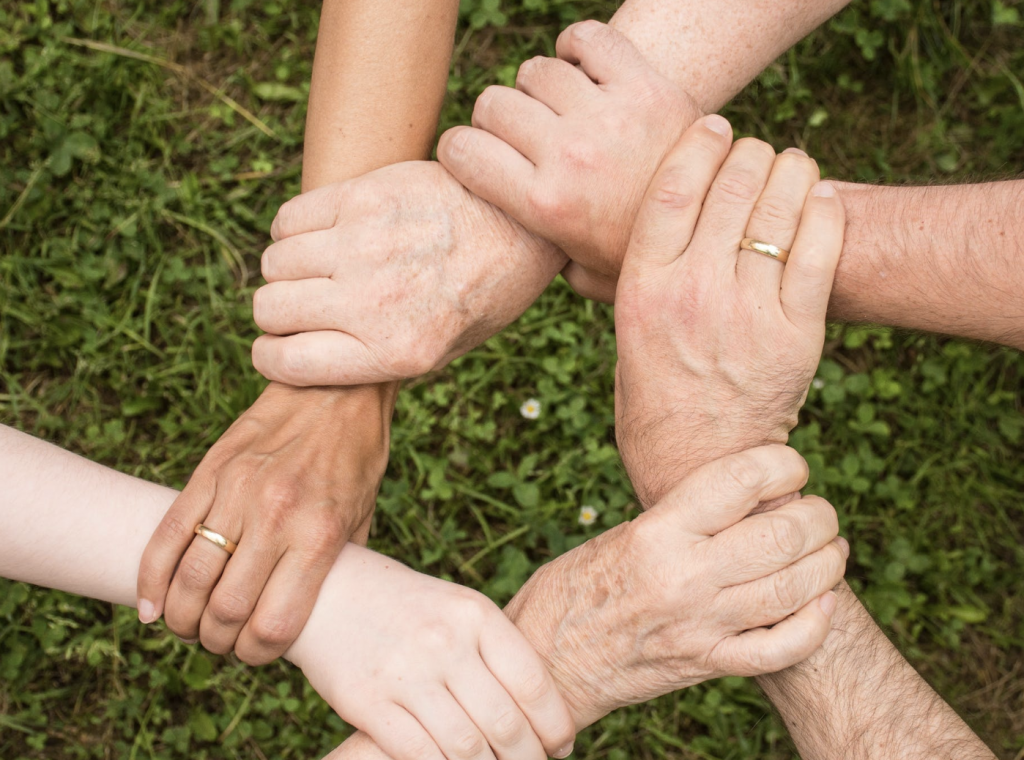 A group of hands interlock featuring people from mixed generations
