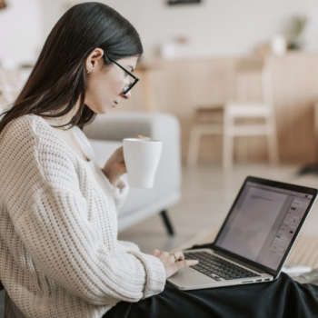 A lady sits on the floor with a computer on her lap and a coffee in her hand hoping for a healthy return to work